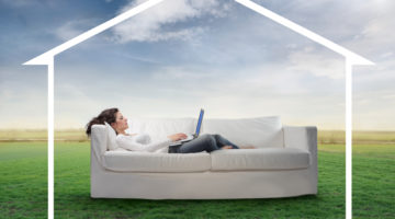 woman on couch working with outline of house