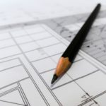 Floor plans with a black pencil on top